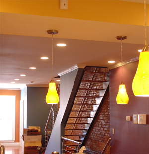 Facing the front. The rich colors balance the industrial quality of the exposed brick and custom banister.