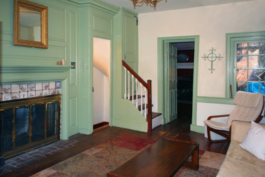The living room, with built-in cabinets, wainscoting and a tile fireplace surround.
