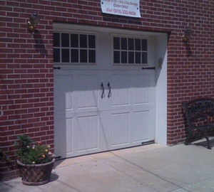 This is a beautiful, old world styled,garage door. The paneled style and small square windows resemble colonial doors, which are common in this area. The owners have placed a welcoming bench and flowerpot to add curb appeal.