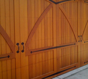 The stained ;wood and ironwork on this garage door is quite lovely. The front door of this row house has a coordinating design.